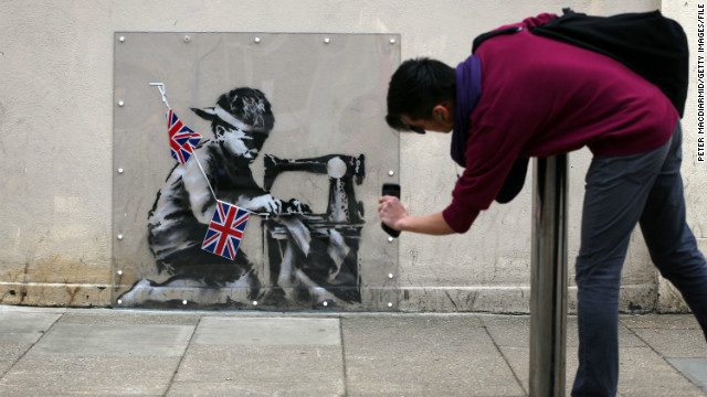"A man takes a photo of the artwork ""Slave Labour,"" attributed to Banksy, on May 17, 2012, in London."