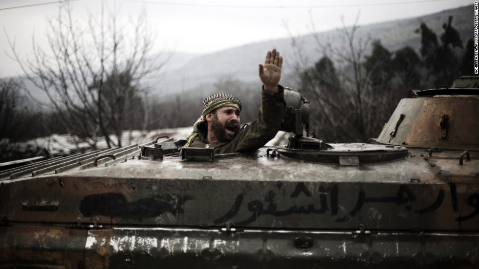 A Syrian rebel gestures at comrades from inside a broken armored personnel carrier in Al-Yaqubia on February 6.