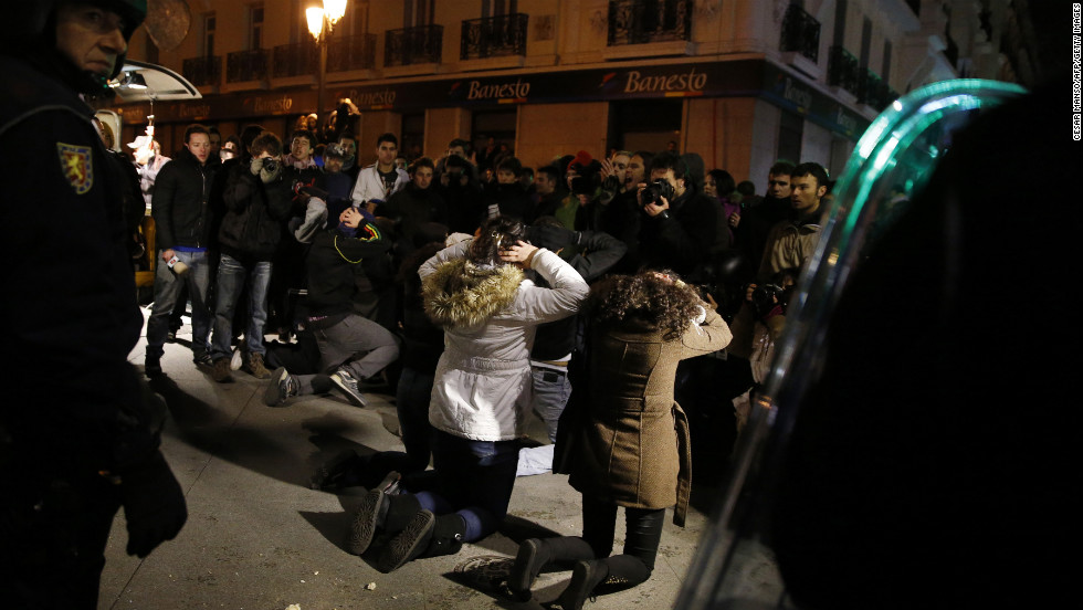 Protesters face Spanish riot police at the end of the demonstration in Madrid.