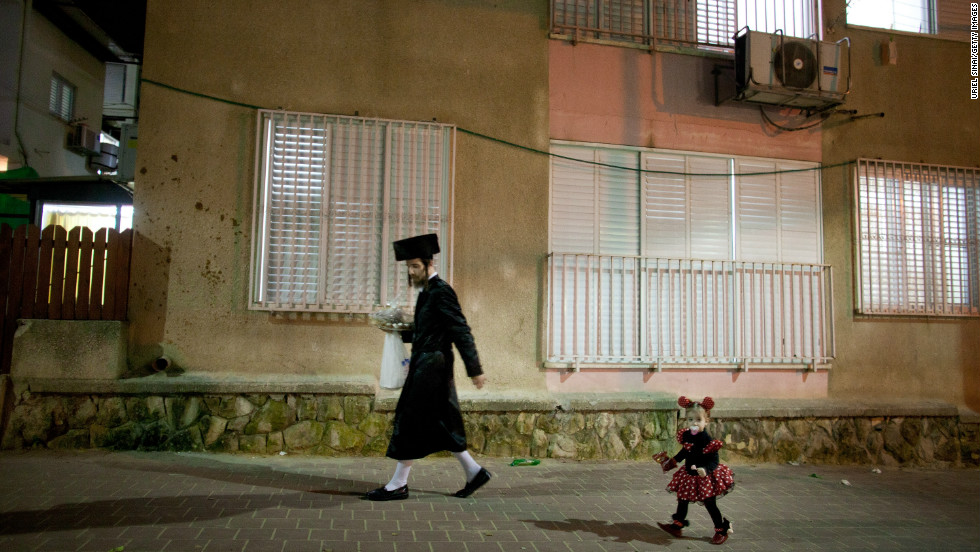An Ultra-Orthodox Jew walks the street with his child as she wears a costume on February 23, 2013 in Bnei Brak, Israel.