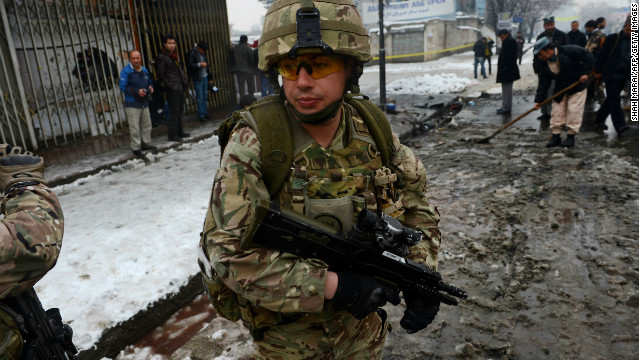 An ISAF soldier stands at the scene of an attack against a bus carrying Afghan army personnel in Kabul on February 27, 2013.