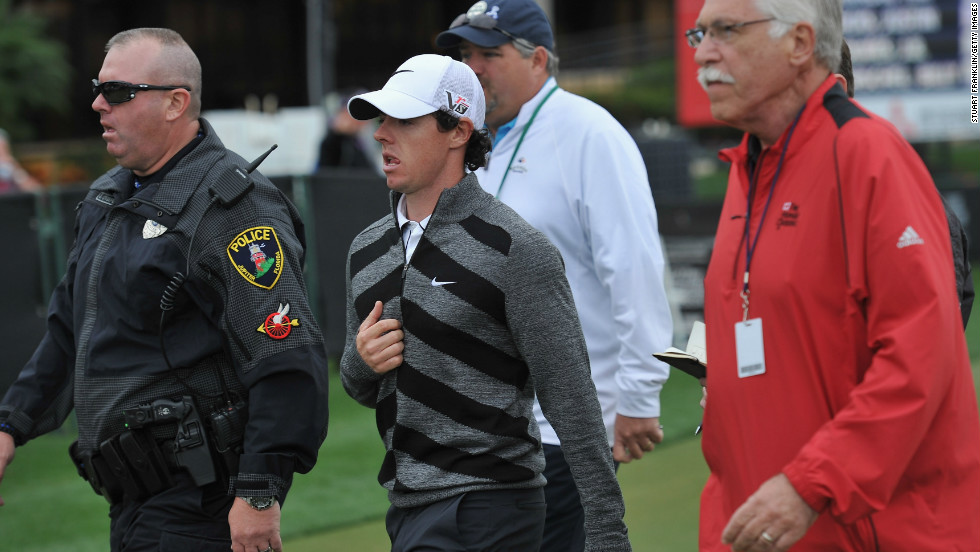 Flanked by officials and security, McIlroy makes a quick exit from the course at Palm Beach Gardens in Florida.