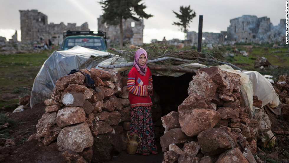 A Syrian girl stands at the entrance of a makeshift home near ruins in Serjilla, Syria, in February 2013.