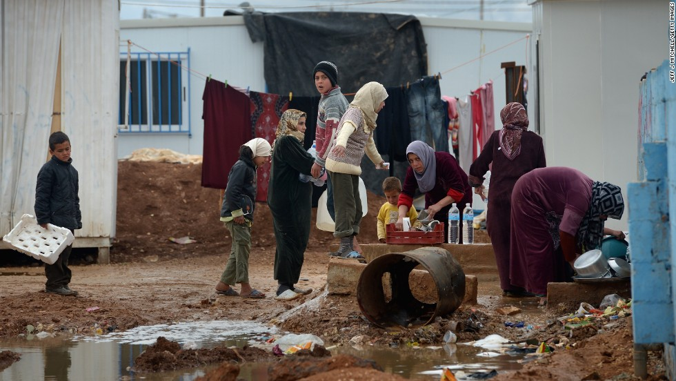 Syrian children gather around women washing in the Zaatari refugee camp in January 2013.
