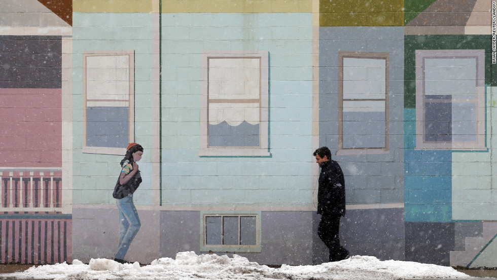 A pedestrian walks past a mural at the beginning of a winter storm in Somerville, Massachusetts, on Thursday, March 7.