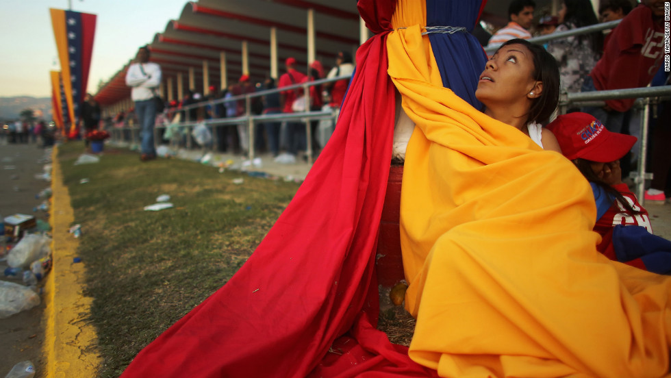 A woman wraps up in Venezuela's flag to stay warm as she and others wait in line before the start of Chavez's funeral.