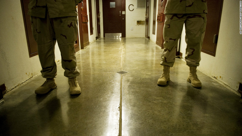 Members of the military move down the hallway of Cell Block C in the Camp 5 detention facility in January 2012.