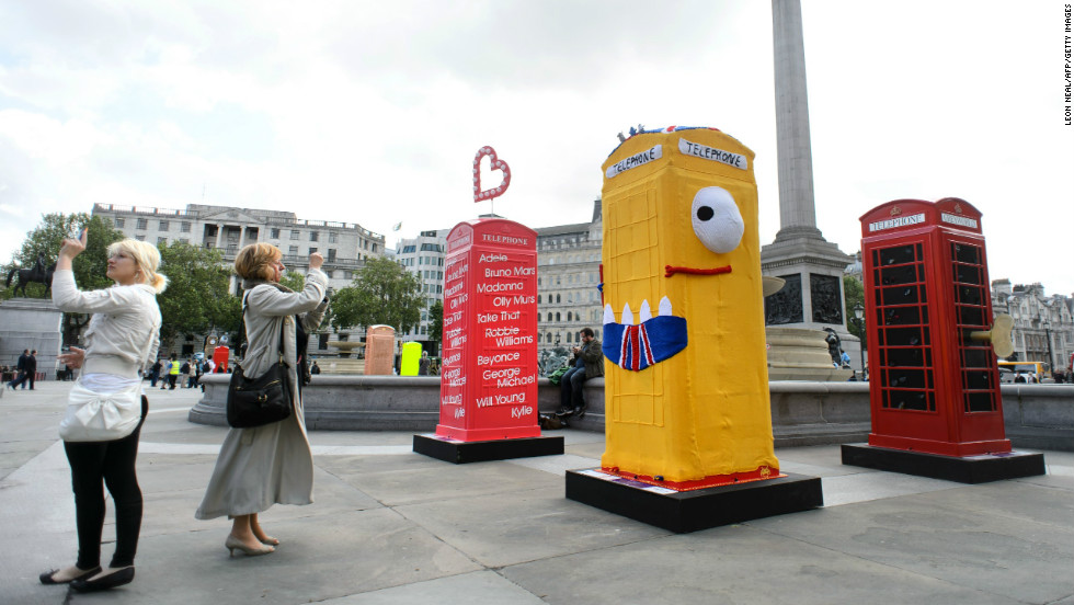 Another artistic statement. People take photographs of decorated replica telephone boxes on display in Trafalgar Square in central London.