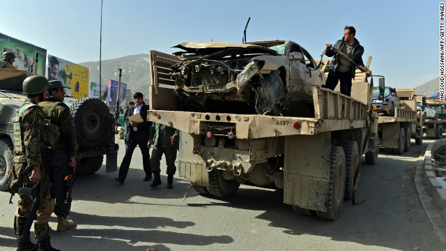 Afghanistan National Army soldiers remove a destroyed car at the site of a suicide attack next to the Defense Ministry in Kabul.