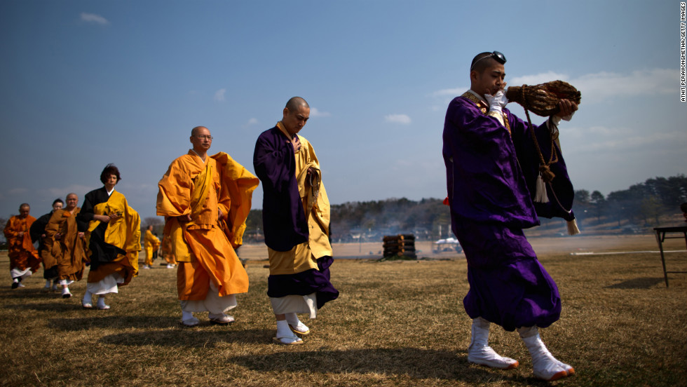 Japanese Buddhist monks chant and pay their respects to the victims on Sunday in Minamisoma.