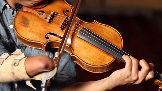 One handed violinist plays, helps others