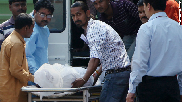 Hospital staff and family members of Ram Singh transport his body into an ambulance on Tuesday.