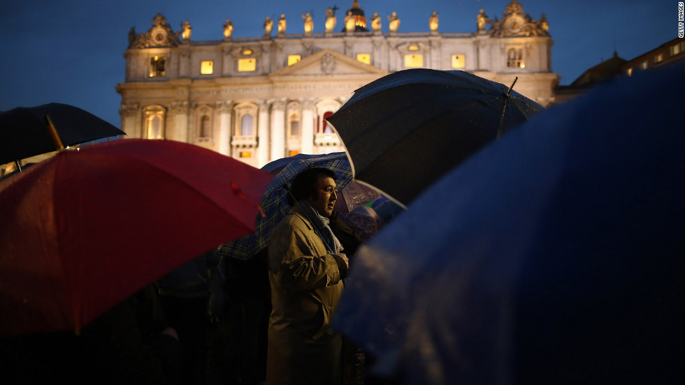 People shield themselves from the rain in St. Peter's Square after the election of the new pope.