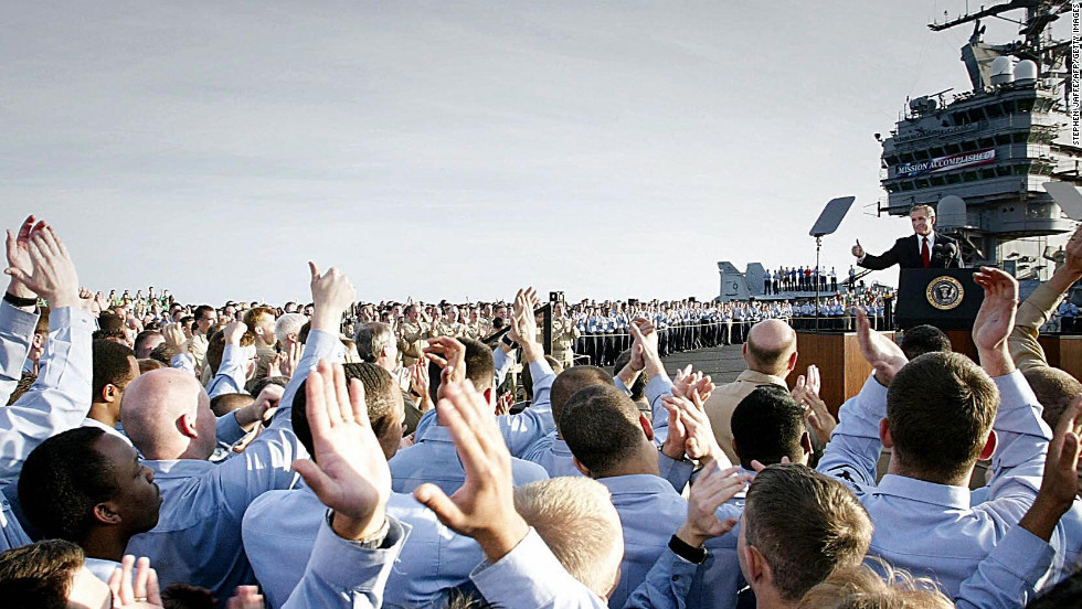 "Sailors applaud as President Bush addresses the nation aboard the USS Abraham Lincoln on May 1, 2003. Standing beneath a banner that read ""Mission Accomplished,"" the president declared major fighting over in Iraq and called it a victory in the ongoing war on terrorism."