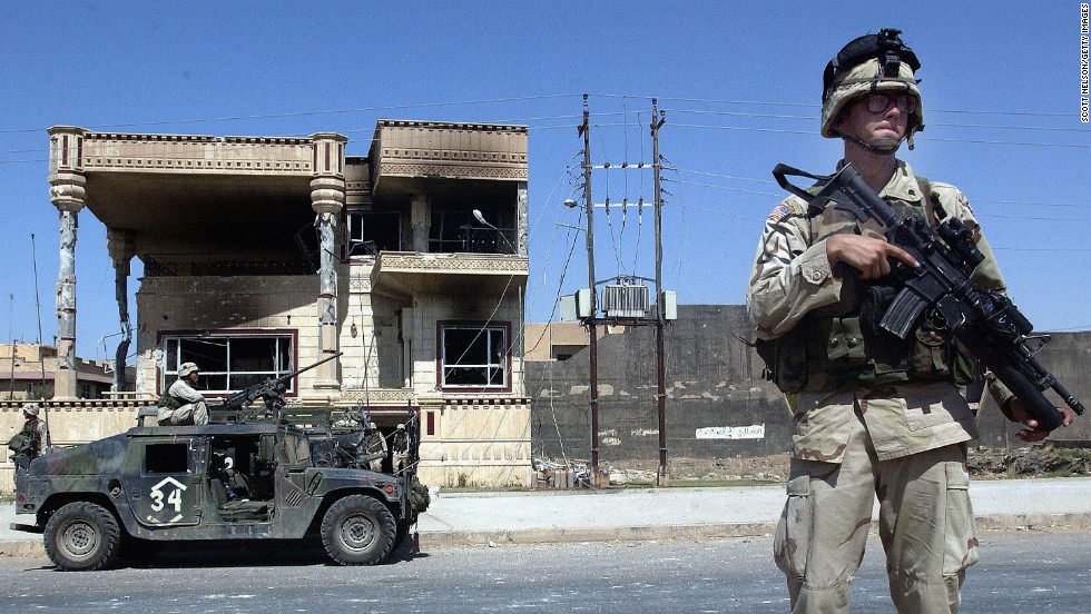 U.S. Army 101st Airborne troops investigate a house where Saddam Hussein's sons Uday and Qusay were killed in Mosul, Iraq, on July 23, 2003. The house, in an affluent neighborhood, was the scene of a fierce gunbattle.