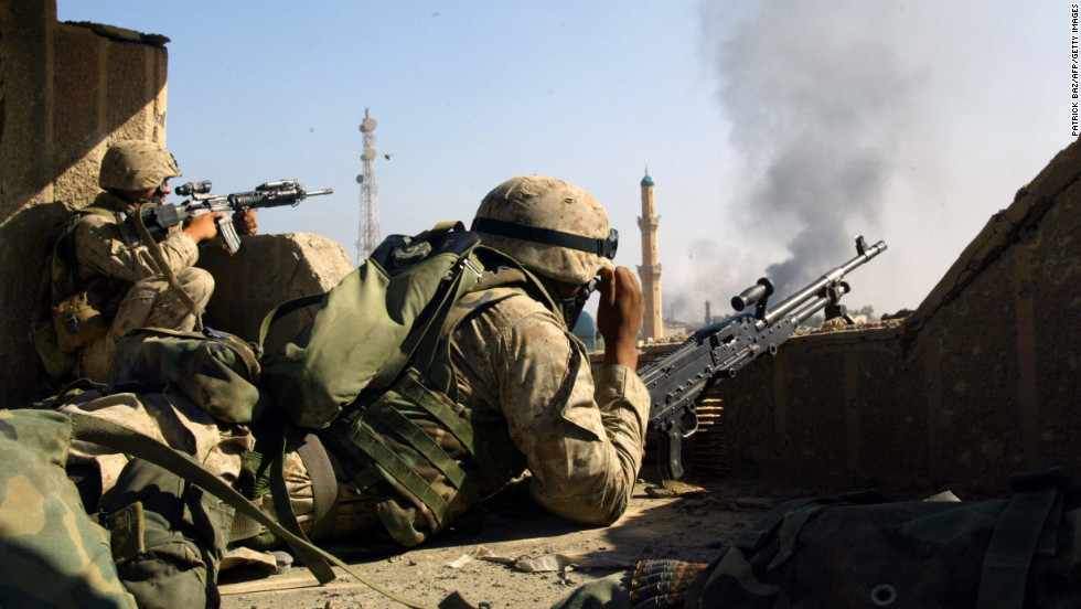 Marines take position on a roof in the restive city of Fallujah on November 13, 2004.