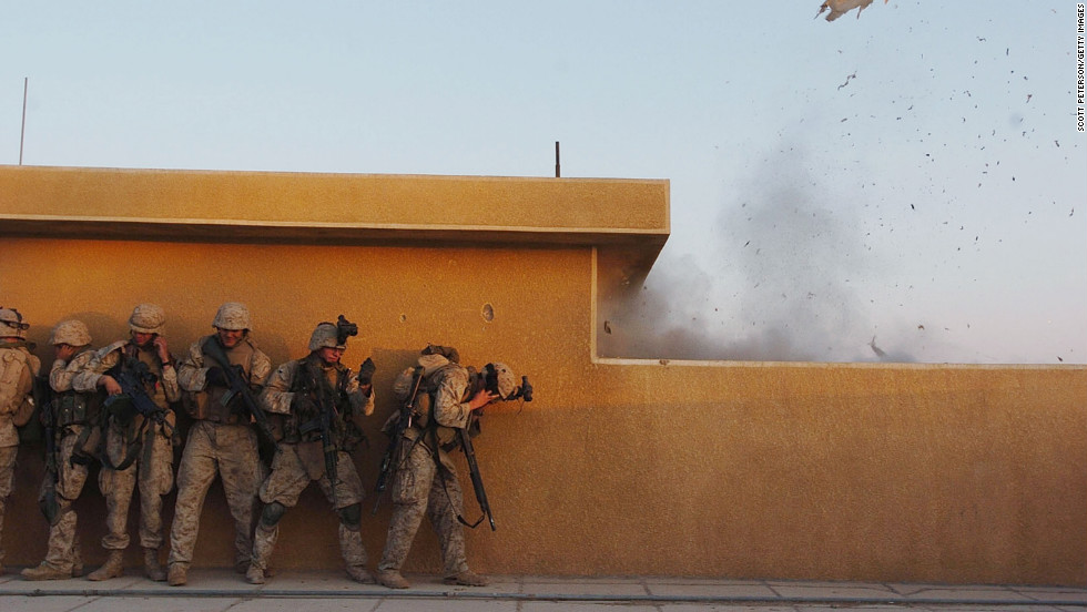 Marines use explosives to open rooftop doors while searching houses in Fallujah for insurgents on November 22, 2004.