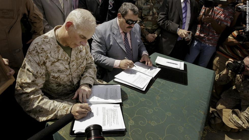 Maj. Gen. John Kelly, left, and Anbar province Gov. Maamoun Sami Rashid al-Alwani sign papers during a handover ceremony in Ramadi on September 1, 2008. The U.S. military turned over security control of Iraq's biggest province, once a stronghold of the Sunni insurgency.