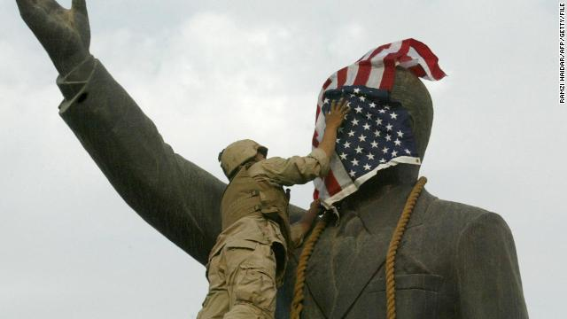 A U.S. Marine covers the face of Iraqi President Saddam Hussein's statue with the U.S. flag in Baghdad on 09 April 2003.