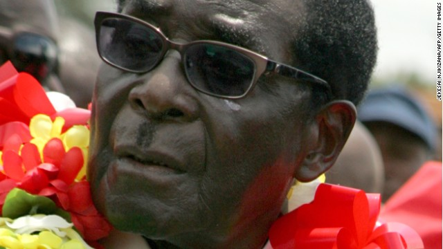 Zimbabwe's President Robert Mugabe wears a garland during a rally held on March 2, 2013 in Bindura,