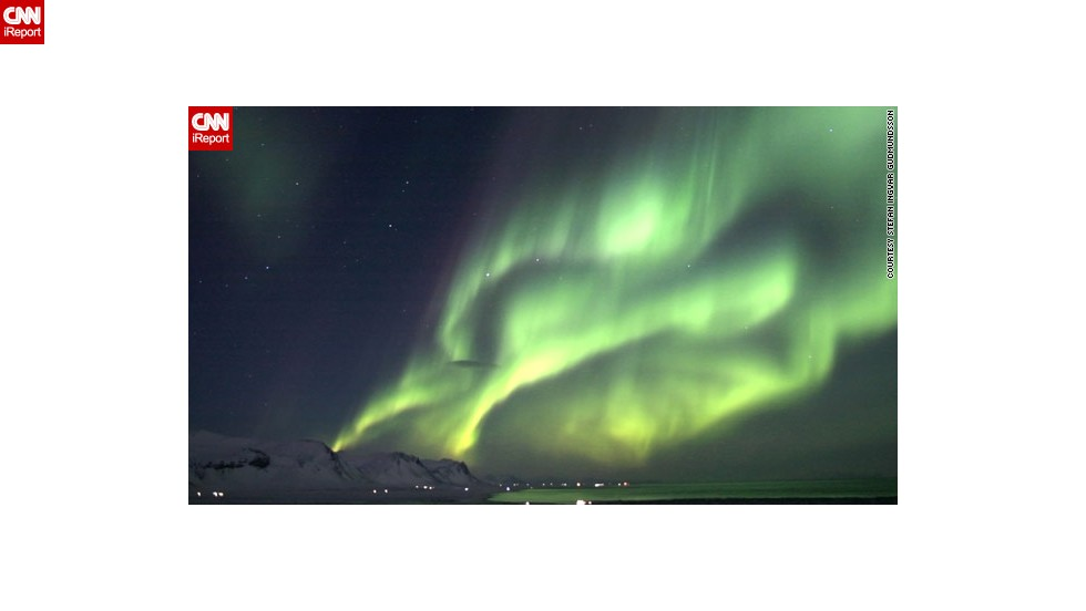 "The lights of the Icelandic village of Olafsvik <a href=""http://ireport.cnn.com/docs/DOC-943369"">are dwarfed </a>by the northern lights in another image from Gudmundsson."