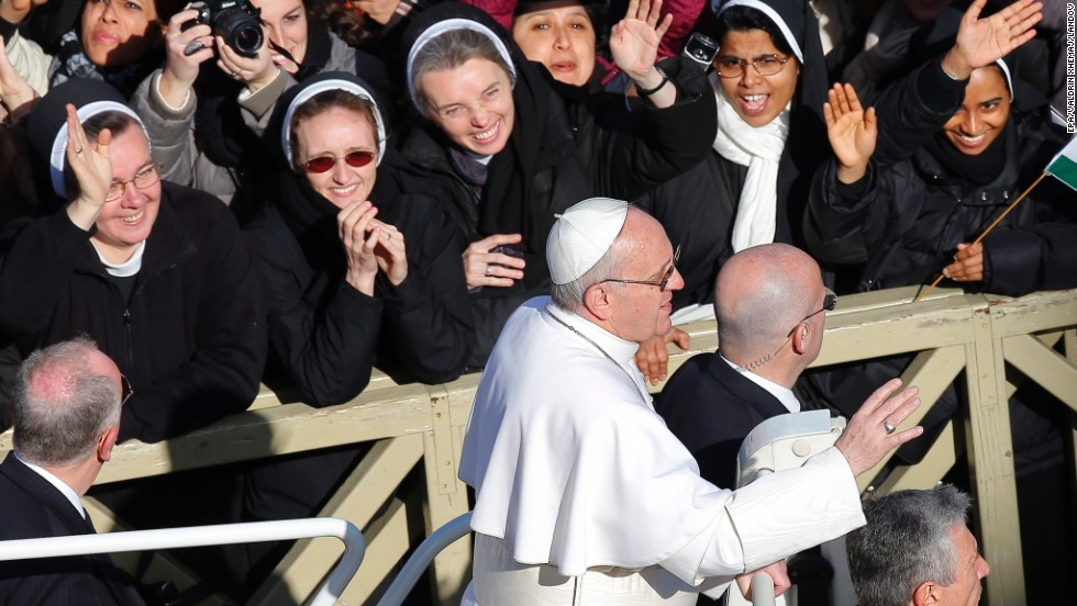 Nuns wave to Pope Francis upon his arrival at the square.