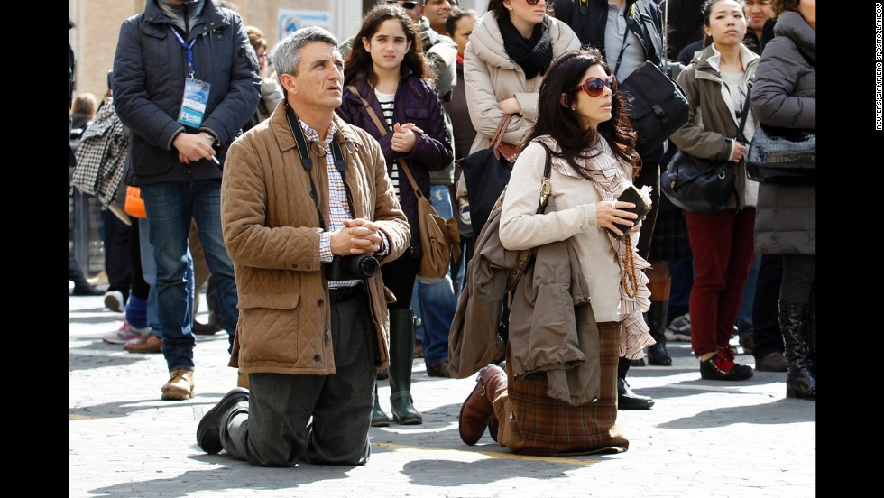 A man and woman pray in St. Peter's Square on March 19.
