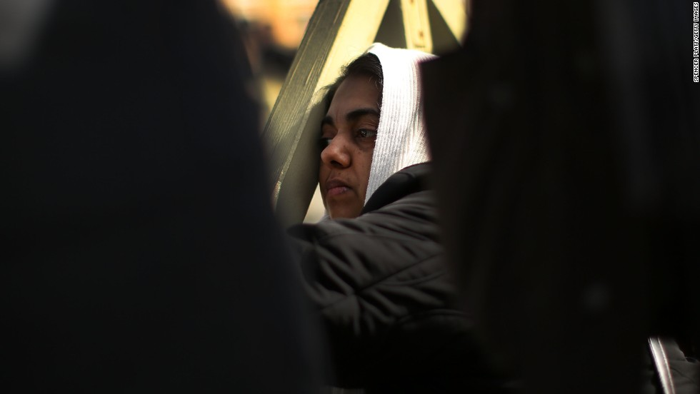 A woman prays during the inauguration Mass.