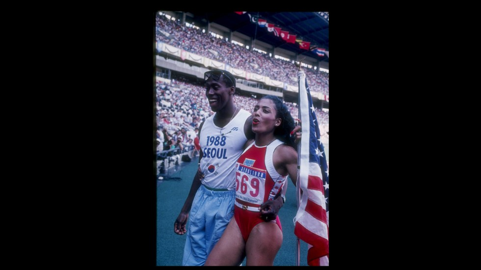 Florence Griffith-Joyner, known as Flo Jo, and Al Joyner, Olympic gold medal winning triple jumper and Flo Jo's coach, met at the U.S. Olympic trial in 1980 and married in 1987. Flo Jo won golds in both the 100 meter and 200 meter at the Seoul Olympics in the following year. She died in 1998. Pictured, she walks off the track with her husband Al Joyner during the Olympic Games in Seoul, South Korea, 1988.