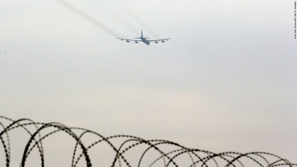 A B-52 bomber flies over the wire-topped fence of a U.S. air base in Osan, South Korea, on Tuesday, March 19.