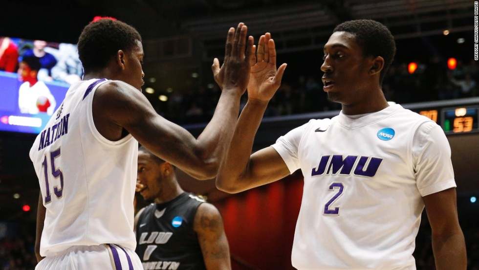 Ron Curry and Andre Nation of the James Madison Dukes celebrate as time winds down against LIU Brooklyn on March 20.