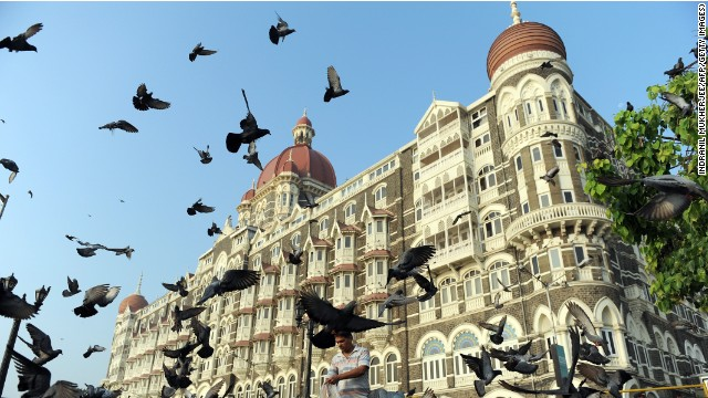 An Indian man (C) feeds pigeons outside the Taj Mahal Palace hotel on the second anniversary of the November, 2008 terror attacks in Mumbai on November 26, 2010.
