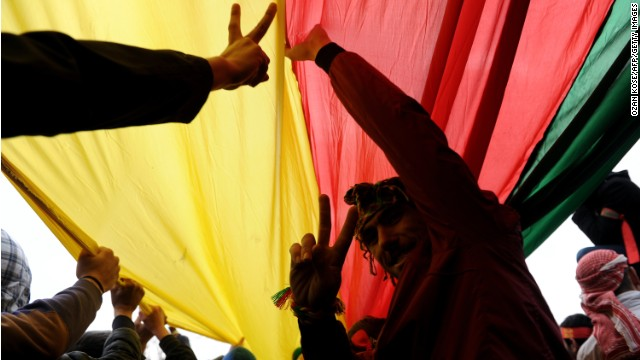 Kurds hold a giant flag of PKK (Kurdish Workers Party) and flash V-signs during celebrations on March 17, 2013 of Nowruz, the Persian New Year festival, in Kazlicesme, Istanbul.