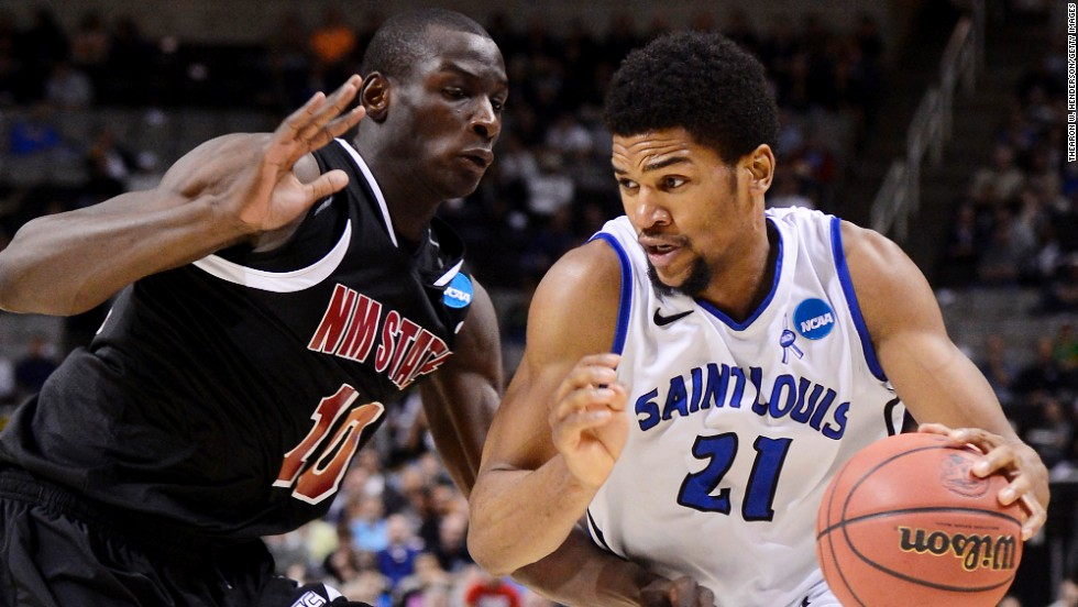 Dwayne Evans of the St. Louis Billikens drives against Bandja Sy of the New Mexico State Aggies on March 21 in San Jose, California.