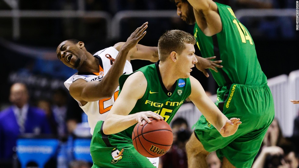 Arsalan Kazemi of Oregon, No. 14, is called for an offensive foul on Markel Brown of Oklahoma State as E.J. Singler of Oregon drives down court on March 21.