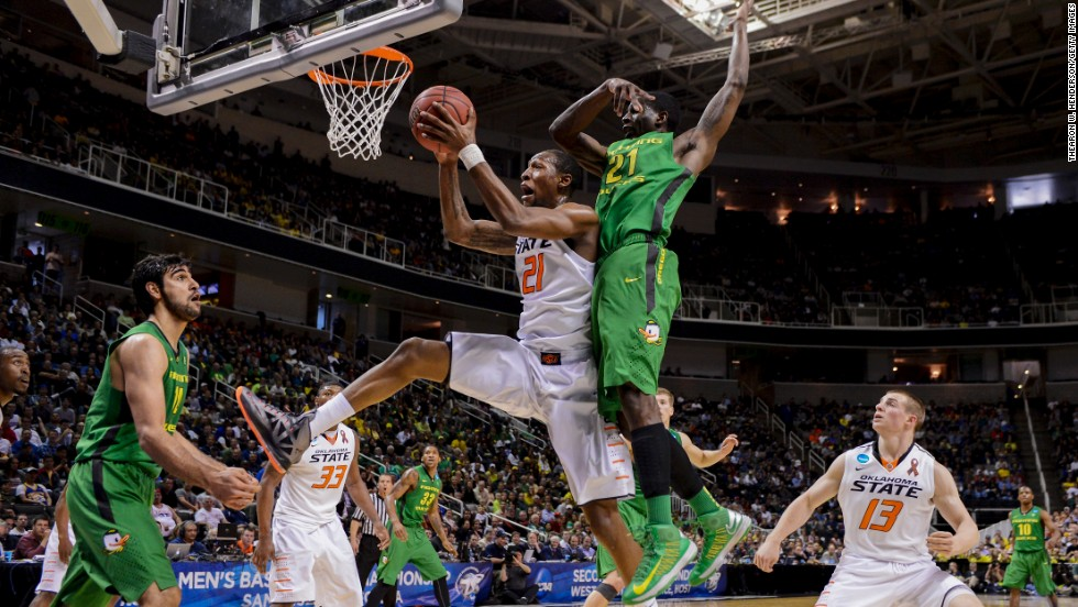 Kamari Murphy of the Oklahoma State Cowboys shoots after grabbing the rebound against Damyean Dotson of the Oregon Ducks on March 21 in San Jose, California.
