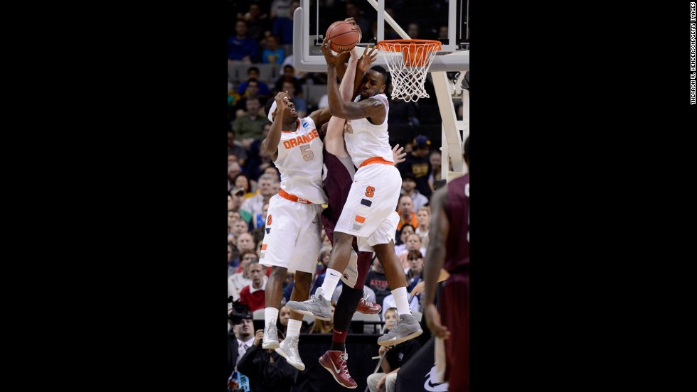 Rakeem Christmas, right, and C.J. Fair, left, of Syracuse go for a rebound against Eric Hutchison of Montana on March 21.