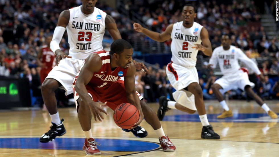 Sam Grooms of the Oklahoma Sooners, center, attempts to control the ball against DeShawn Stephens, left, and Xavier Thames of the San Diego State Aztecs on March 22 in Philadelphia.