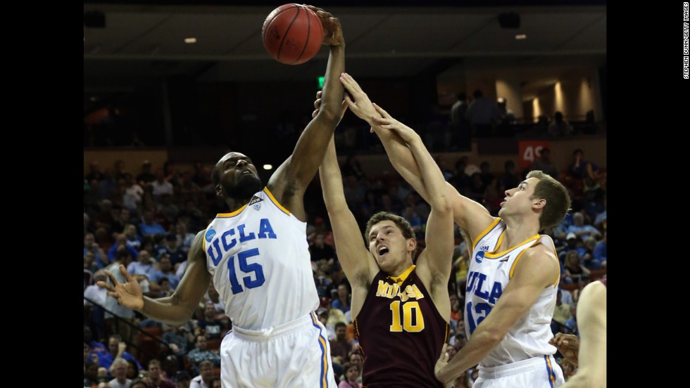 Oto Osenieks of the Minnesota Golden Gophers, center, goes between Shabazz Muhammad, left, and David Brown of the UCLA Bruins on March 22.