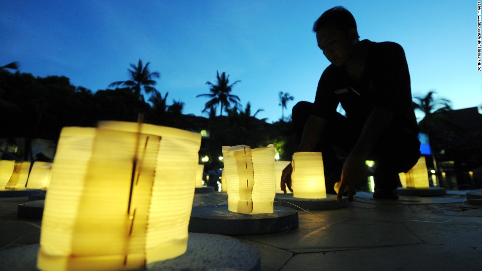 Balinese men burn lanterns during Earth Hour at a hotel in Nusa Dua on the resort island of Bali.