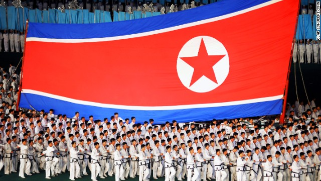 A large group of Taekwondo fighters carries the North Korean National Flag as a sign of pride, honor and victory at a sports performance during the Arirang Mass Games in Pyongyang, August 8, 2012. The Mass Games are a huge spectacle with thousands of participants. During the Mass Games sports, dance and gymnastic performances are presented. The event takes place inside the huge Rungrado May Day Stadium.