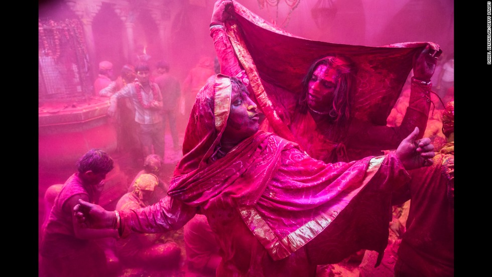 Transgender revelers dance as others play with color on March 21 in Barsana.