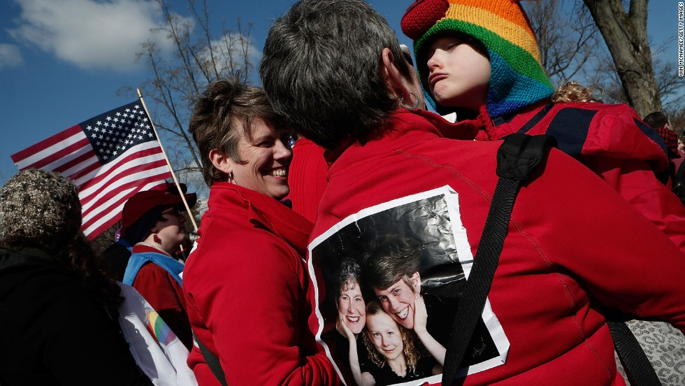 The Rev. Rebecca Voelkel, left, partner Maggie George and their daughter Shannon Voelkel take part in Tuesday's demonstrations in front of the Supreme Court.
