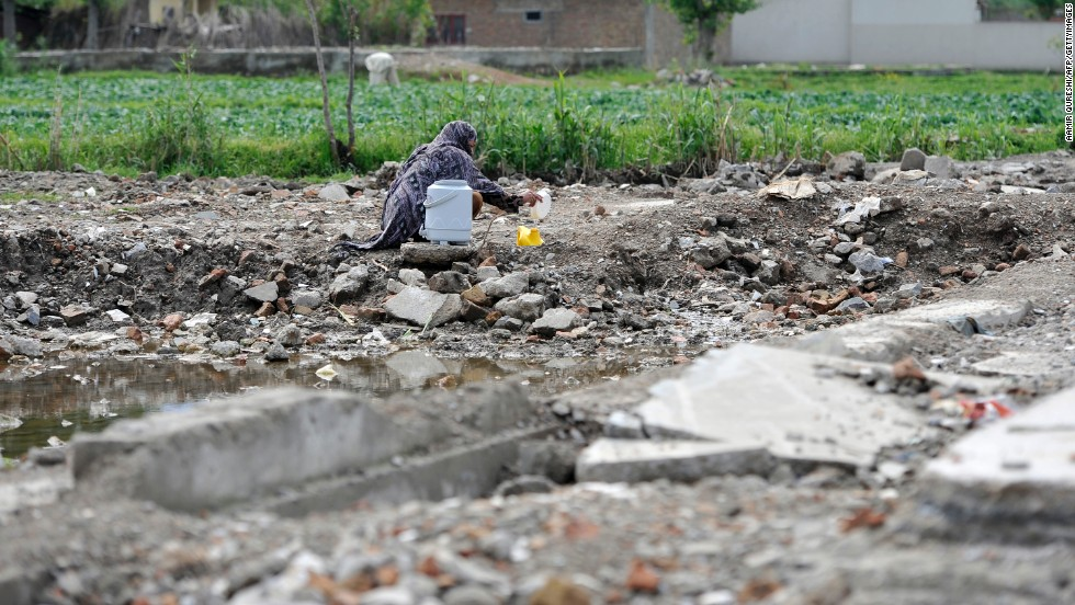 A Pakistani woman fills a container with water at the site of the demolished compound on April 25, 2012.