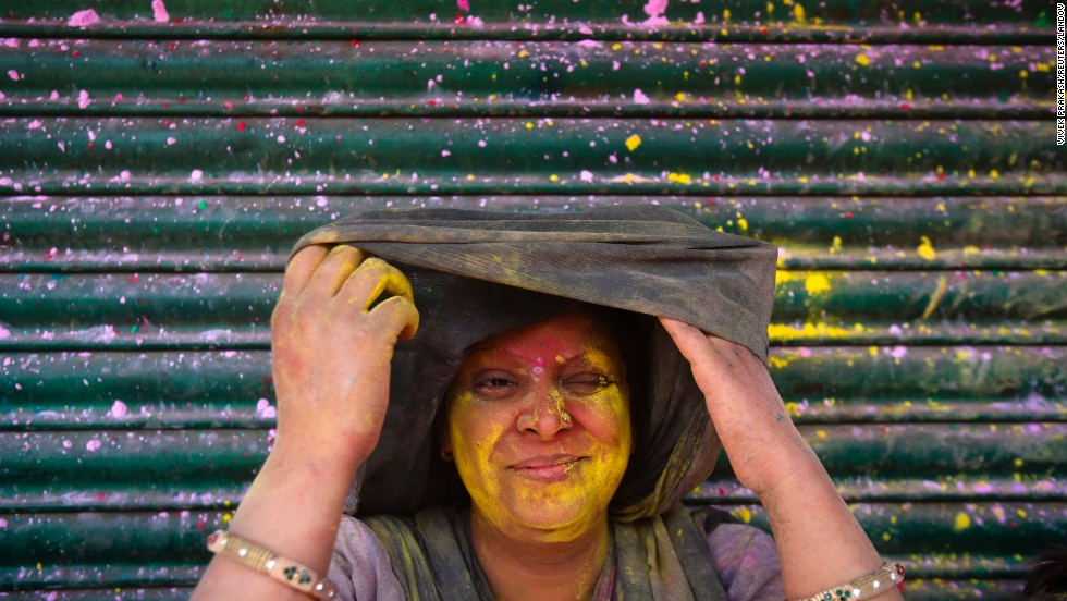 A woman squints as she looks out from under her veil after being smeared in colored powder in Vrindavan, India, on March 27.