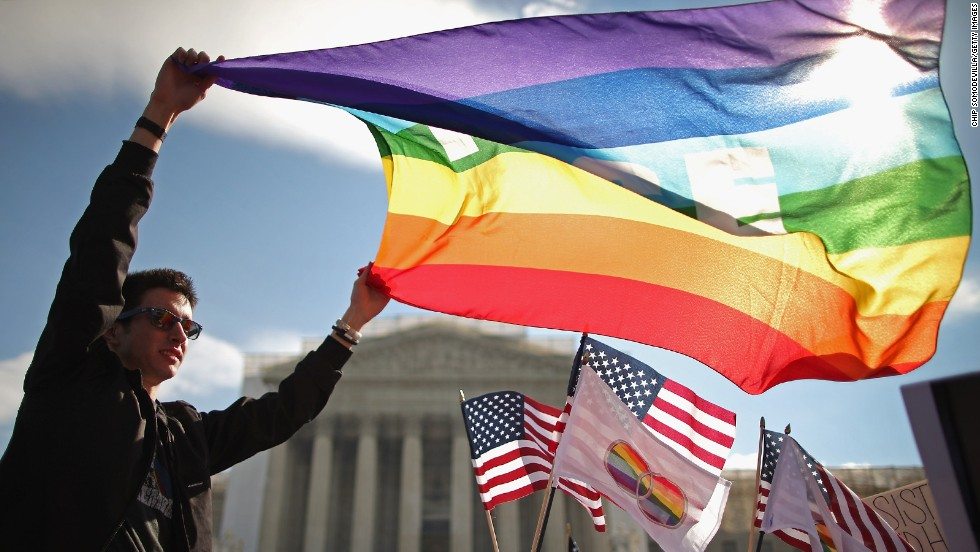 George Washington University student Eric Breese waves a rainbow flag outside the court Wednesday.