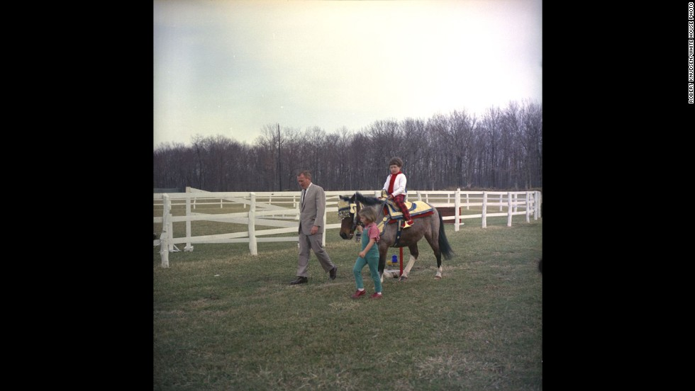 "Sally Fay, the daughter of the Navy under secretary, rides Caroline Kennedy's pony, Macaroni, as her father and Caroline Kennedy walk alongside. ""Macaroni"" is wearing a Moroccan saddle, which was given to Caroline by King Hassan II of Morocco during his state visit earlier that month."