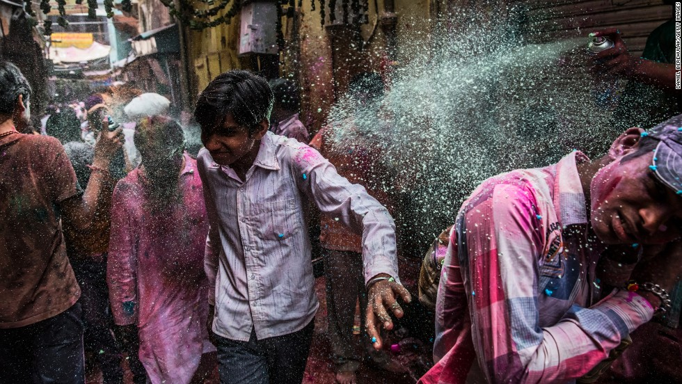 A man sprays a colored substance from an aerosol can on passersby during Holi on March 27 in Vrindavan.