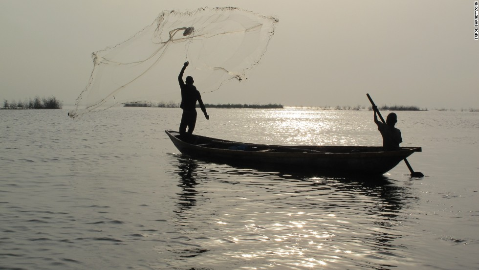 A fisherman throws out his net on the lagoon's calm waters. Fisherman immigrating from Benin and Togo initially settled Makoko over a century ago. But as the population of Lagos exploded to its current size of at least 15 million, so too did the population of Makoko. Estimates are anywhere from 85,000 to 250,000 people live there.