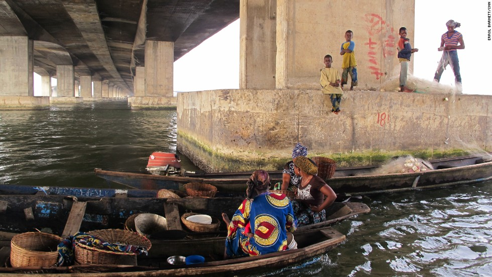 "Women and children congregate under the Third Mainland Bridge, which connects Lagos Island with Nigeria's mainland. CNN's Errol Barnett describes the image as representing two separate worlds, ""Many who travel over this bridge daily tell me they've never been to Makoko and don't know what life is like for people living there."""